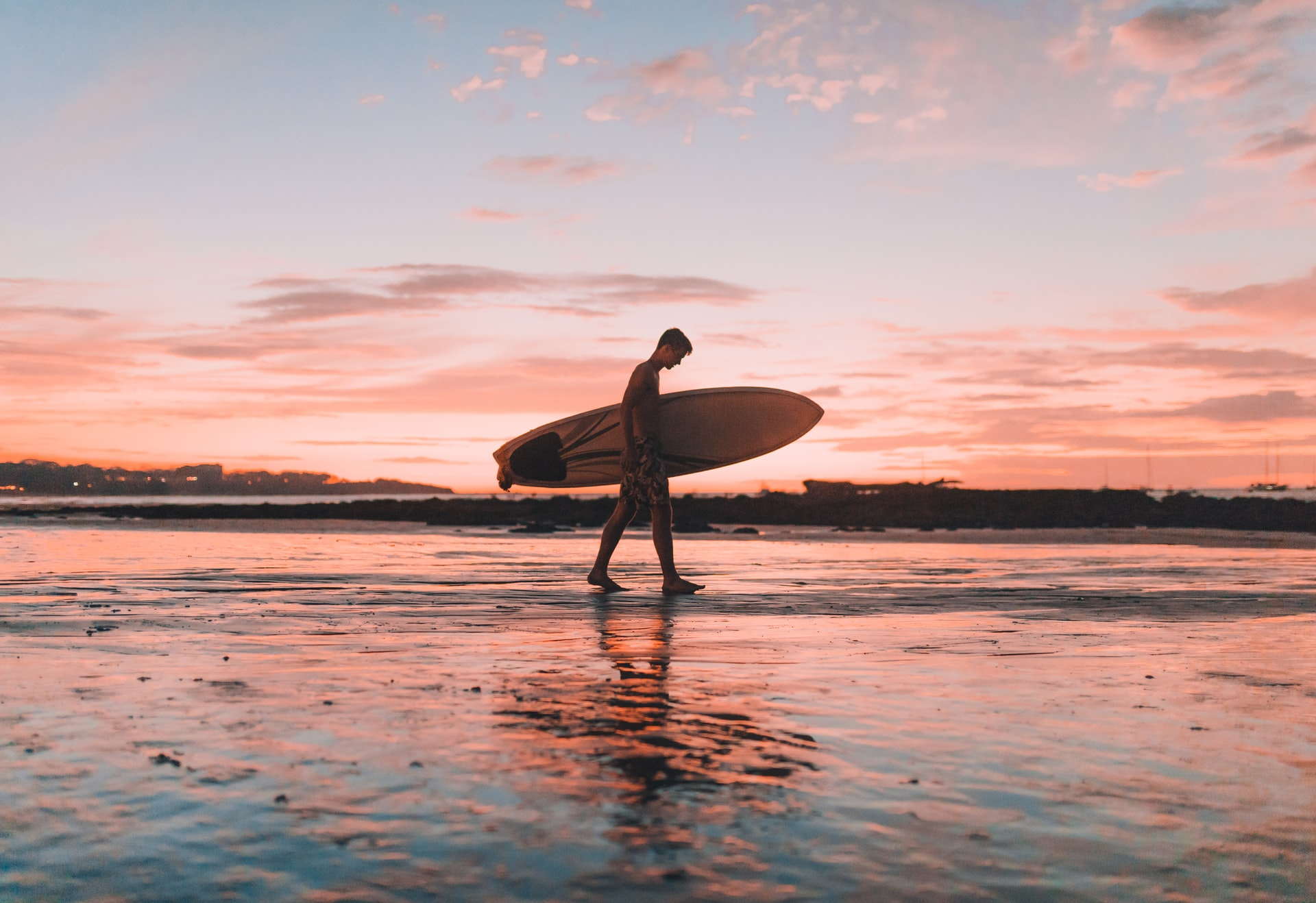 Man holding a swallow tail surfboard